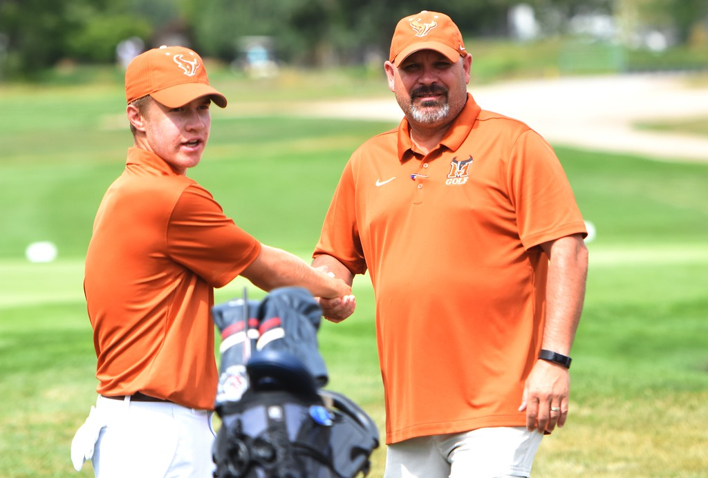 . Mead\'s TJ Shehee is congratulated by Mavericks head coach Mike Ward on the 18th green after winning the 4A Region 3 championship on Wednesday at the Olde Course in Loveland.