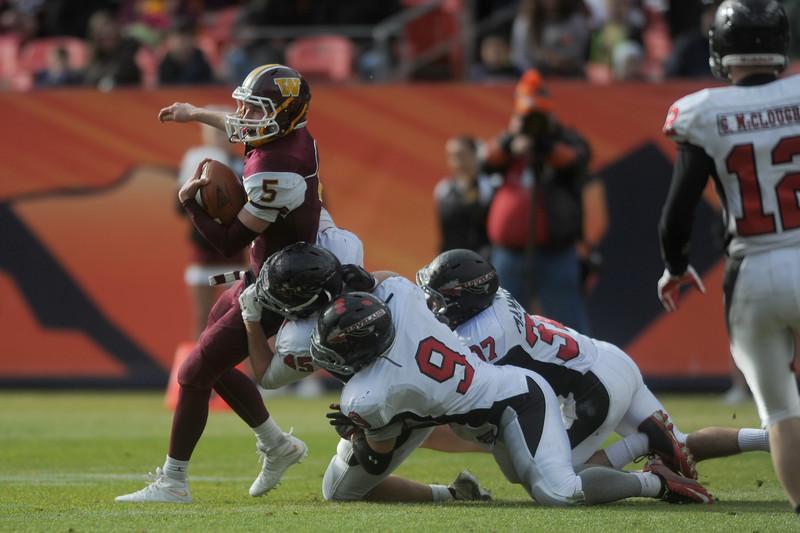 Brad Peeples (5), Windsor quarterback, taken down by Loveland High's Ryan Svendsen (45), Dylan Jackson (9) and Manny Mammoser (37) on Saturday, Dec. 5, 2015 in Denver. (Photo by Trevor L. Davis/Loveland Reporter-Herald)