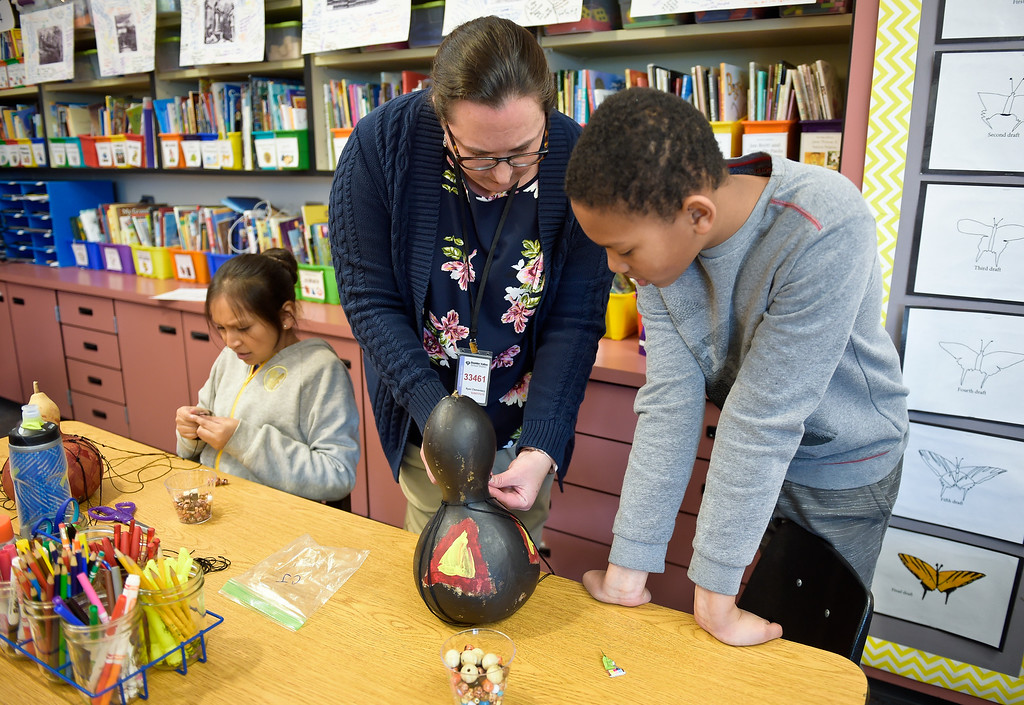 """. LAFAYETTE CO - MARCH 11: Fifth grader CJ Carroll, right, gets help from Ruth Edwards, center, as fifth grader Sarahi Martinez-Davila, left, work on African gourd percussion instruments at Ryan Elementary March 11, 2019. Ryan Elementary is putting on \""""A Walk Through Time\"""" event on the slave trade this week. To view more photos visit dailycamera.com. (Photo by Lewis Geyer/Staff Photographer)"""