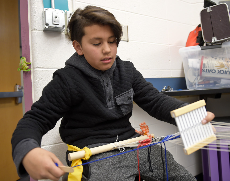 """. LAFAYETTE CO - MARCH 11: Fifth grader Fabo Gonzales works on a weaving project at Ryan Elementary March 11, 2019. Ryan Elementary is putting on \""""A Walk Through Time\"""" event on the slave trade this week. To view more photos visit dailycamera.com. (Photo by Lewis Geyer/Staff Photographer)"""