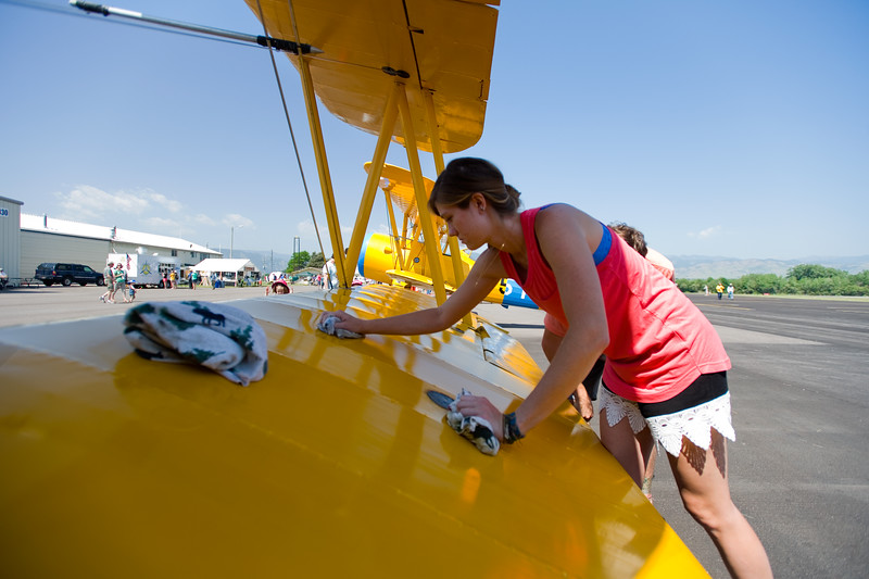 "Paige Dorlac cleans a family-owned N3N-3 naval trainer, that was used during WWII, on display at Airport Day at the Boulder Municipal Airport on Saturday. <br /> More photos:  <a href=""http://www.dailycamera.com"">http://www.dailycamera.com</a><br /> (Autumn Parry/Staff Photographer)<br /> June 18, 2016"