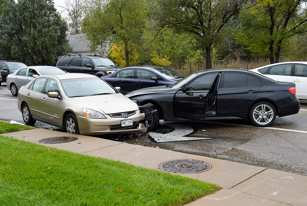 . LONGMONT, CO - OCTOBER 10: The scene of a two-vehicle crash which occurred at Ninth Avenue and Hover Street Oct. 10, 2018. The black BMW was carjacked by an armed suspect in Boulder. (Photo by Lewis Geyer/Staff Photographer)