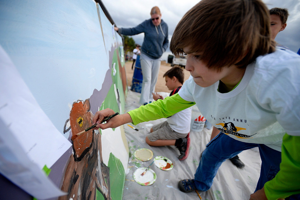 . Felix Feiger, 11, with the Artism program, paints Sebastian the goat while helping to create a mural for the Luvin Arms Farm Sanctuary in Lafayette on Sunday. Kira Horvath / Staff Photographer / April 10, 2016