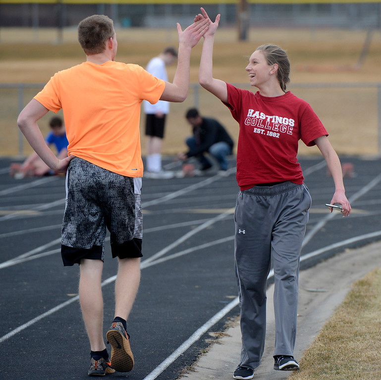. Berthoud\'s Samantha Mulder, right, gives a high-five to Dawson Visger during a March 1, 2018 practice at Berthoud High School. (Sean Star/Loveland Reporter-Herald)