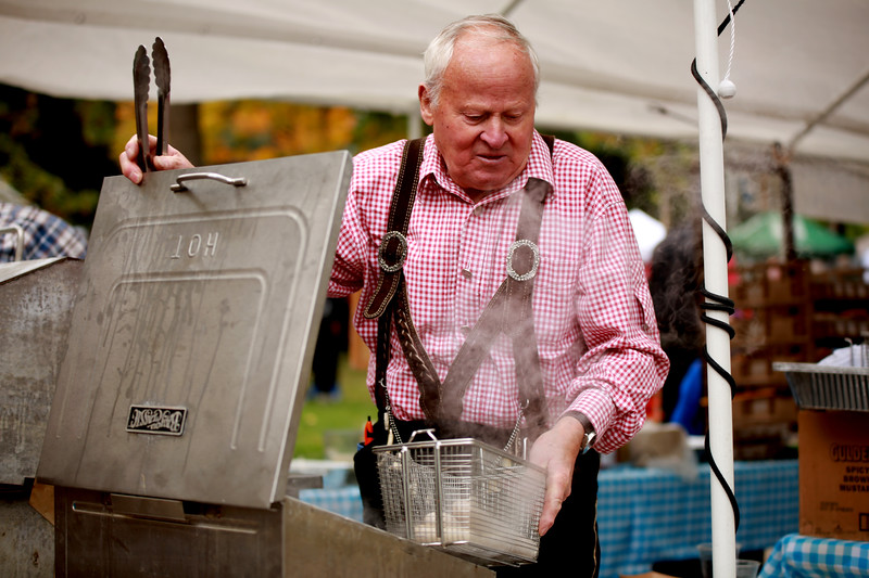 Walter Knoedlseder grills some bratwursts at Styria Bakery's booth at Berthoud's Oktoberfest in Fickle Park on Oct. 6, 2018 in Berthoud.<br /> Photo by Taelyn Livingston/ Loveland Reporter-Herald.