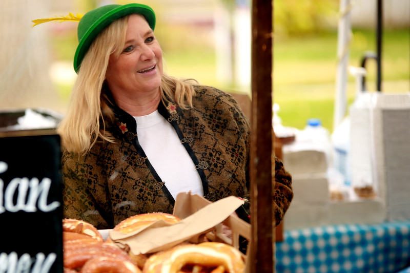 Belinda Powell serves Bavarian pretzels from Styria Bakery's booth at Fickle Park during Berthoud's Oktoberfest on Oct. 6, 2018 in Berthoud.<br /> Photo by Taelyn Livingston/ Loveland Reporter-Herald
