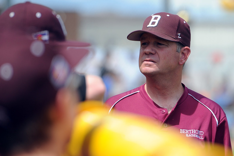 Berthoud coach Buddy Kouns takes a look into the dugout during a game May 5 at Windsor. (Sean Star/Loveland Reporter-Herald)