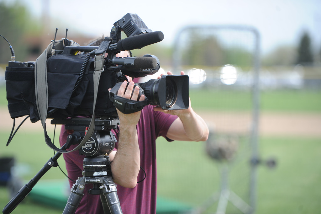 . A cameraman from CBS Denver films Berthoud assistant coach Clint Barmes during a practice May 9, 2018 at Berthoud High School. (Sean Star/Loveland Reporter-Herald)