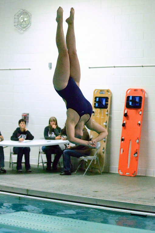 . Mountain View diver Taylor Lenhart looks for the water as she completes a dive during Thursday\'s triangular with Berthoud and Holyoke at the Mountain View Aquatic Center. Lenhart won the event with her first six-dive, state-qualifying score of 227.35. (Mike Brohard/Loveland Reporter-Herald)