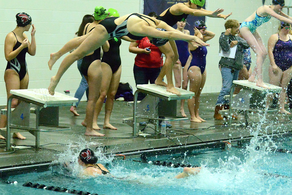 . Berthoud\'s Hanna Roberts dives off the blocks over teammate Abby Dodd during the 200-yard freestyle relay during Thursday\'s triangular with Mountain View and Holyoke at the Mountain View Aquatic Center. (Mike Brohard/Loveland Reporter-Herald)