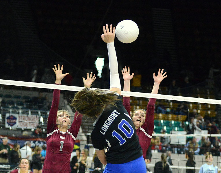 Longmont's Payton Jonason goes over the block of Berthoud's Sophie Kathol (1) and Teagan Holmes (12) in their 4A state tournament match at the Denver Coliseum on Thursday. (Mike Brohard/Loveland Reporter-Herald)