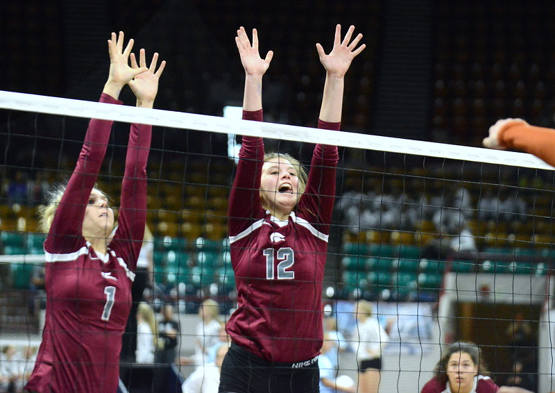 Berthoud's Sophie Kathol (1) and Teagan Holmes rise up for the block in their 4A state match with Mead on Thursday at the Denver Coliseum. The 12th-seeded Spartans knocked off No. 5 Mead with a 31-29, 25-15, 26-24 sweep. (Mike Brohard/Loveland Reporter-Herald)