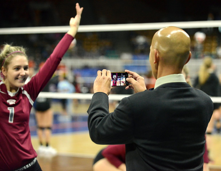 Berthoud's Sophie Kathol hams it up as coach Mil Santos snaps a few photos during warmups for the 4A State Tournament on Thursday at the Denver Coliseum. (Mike Brohard/Loveland Reporter-Herald)