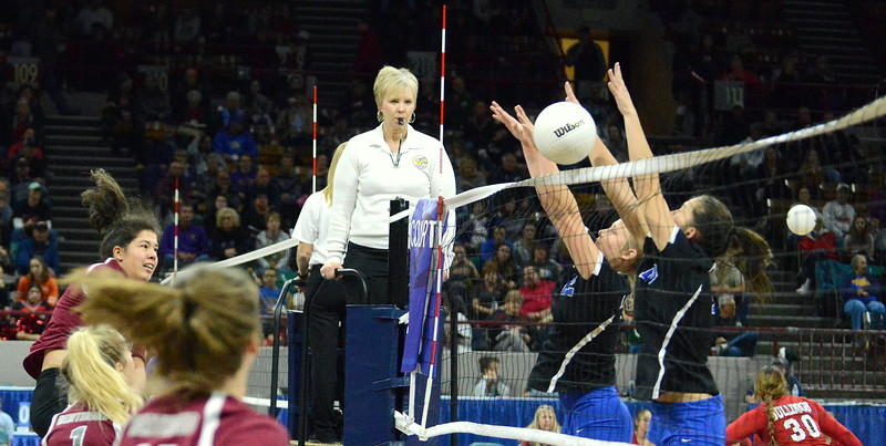 Berthoud's Kailey Berry swings against the block of Longmont's Annika Wetterstrom (2) and Zoe Lowe (13) in their 4A state tournament match at the Denver Coliseum on Thursday. (Mike Brohard/Loveland Reporter-Herald)
