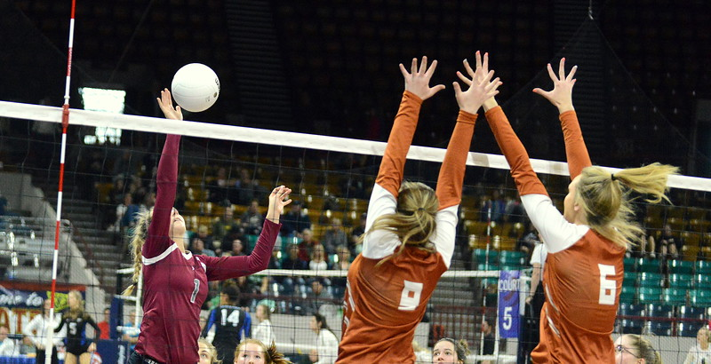 Sophie Kathol of Berthoud goes with the tip to avoid the block of Mead's Kenzie Morton (9) and Abbey Glenn (6) during their 4A state match with Mead on Thursday at the Denver Coliseum. The 12th-seeded Spartans knocked off No. 5 Mead with a 31-29, 25-15, 26-24 sweep. (Mike Brohard/Loveland Reporter-Herald)