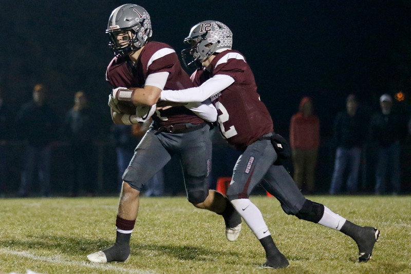 Berthoud's Brock Voth (12) hands off the ball to Jacob Lozinski (1) on Friday, Nov. 3, 2017 at Marr Field in Berthoud. (Lauren Cordova/Loveland Reporter-Herald)