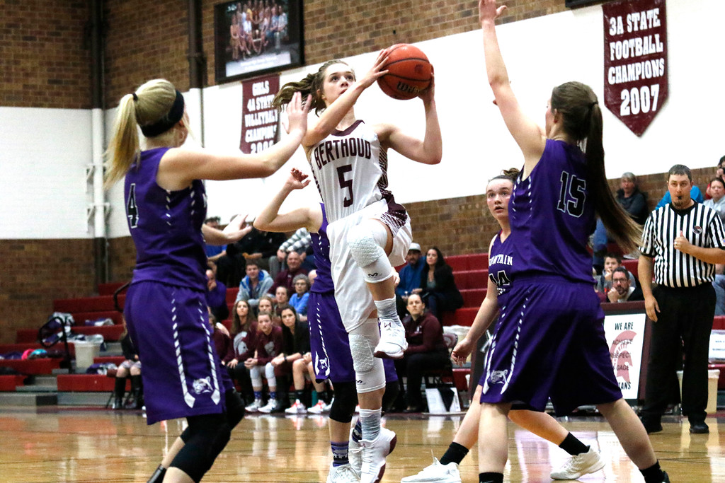 . Berthoud�s Logan Davidson (5) jumps to shoot the ball while Mountain View�s Harley Duke (4) and Makia Hodges (15) try to block her shot on Wednesday, Dec. 6, 2017, at Berthoud High School. (Photo by Lauren Cordova/Loveland Reporter-Herald)