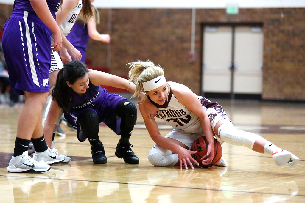 . Berthoud�s Ashlee Burdette (30) protects the ball from being stolen by Mountain View�s Kali Kelley (1) on Wednesday, Dec. 6, 2017, at Berthoud High School. (Photo by Lauren Cordova/Loveland Reporter-Herald)