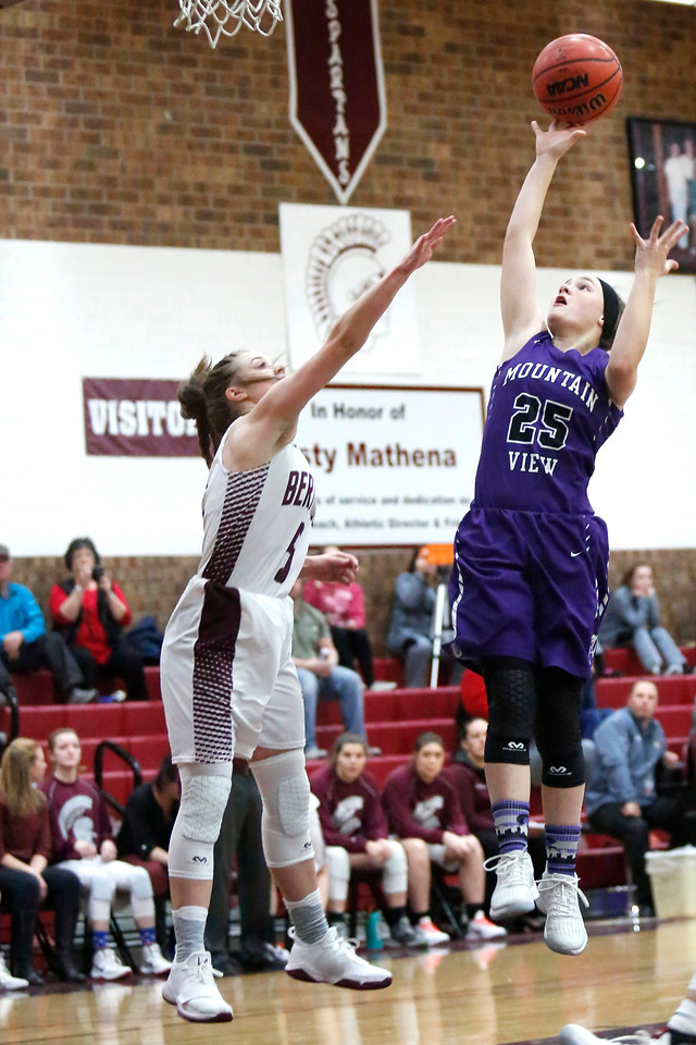 Mountain View's Kelsey Basart (25) jumps to shoot the ball while Berthoud's Logan Davidson (5) tries to block her on Wednesday, Dec. 6, 2017, at Berthoud High School. (Photo by Lauren Cordova/Loveland Reporter-Herald)