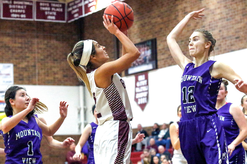Mountain View's Chloe Miller (12) jumps to block Berthoud's Eriana Rennaker's (22) shot on Wednesday, Dec. 6, 2017, at Berthoud High School. (Photo by Lauren Cordova/Loveland Reporter-Herald)