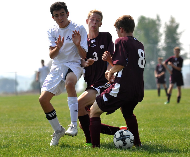 Mountain View's Nate Acuna collides with Berthoud defenders Saturday Sept. 2, 2017 at MVHS. (Cris Tiller / Loveland Reporter-Herald)