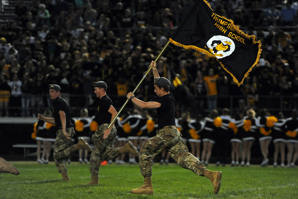 . A member of the Thompson Valley ROTC carries a flag across the field between quarters during a game Friday, Sept. 14, 2018 at Patterson Stadium in Loveland, Colorado. (Sean Star/Loveland Reporter-Herald)