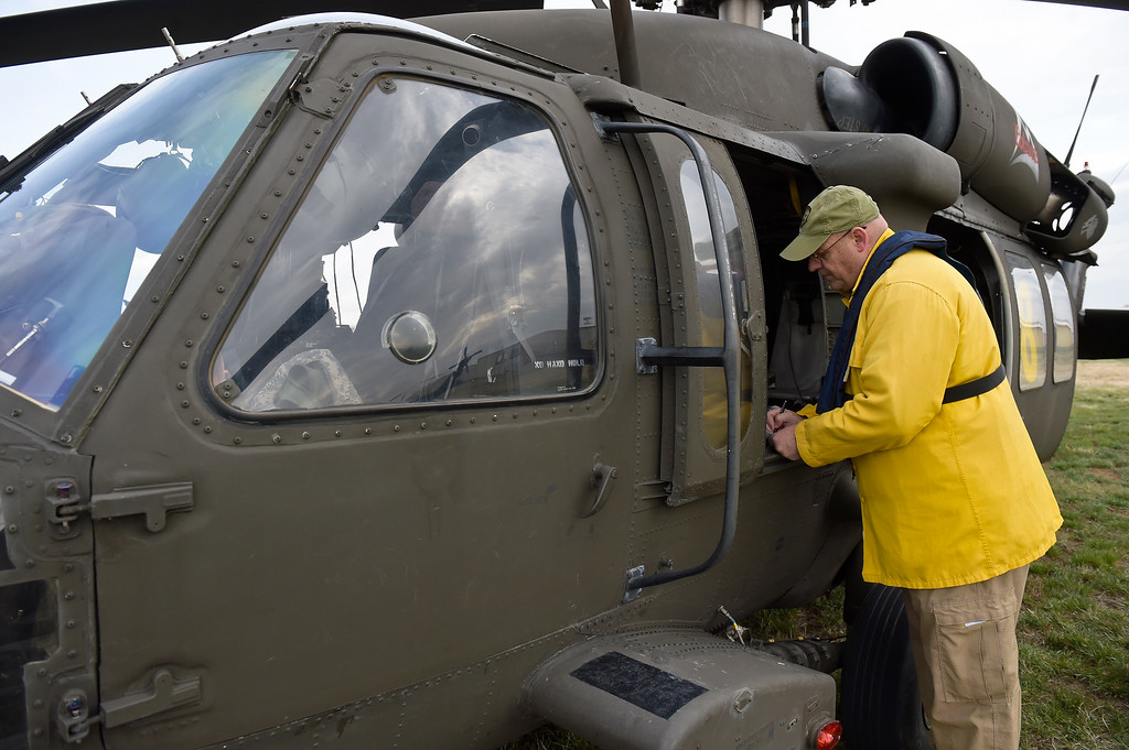 . LONGMONT, CO - APRIL 2: Floyd Keller, with the U.S. Forest Service, fills out paperwork outside a Colorado Army National Guard Black Hawk helicopter at Vance Brand Airport Tuesday morning, April 2, 2019. The Colorado Army National Guard is conducting live bucket training for the next several days at Longmont\'s Ralph Price Reservoir at Button Rock Preserve, four miles west of Lyons. Button Rock will be closed during the training. To view more photos visit timescall.com. (Photo by Lewis Geyer/Staff Photographer)