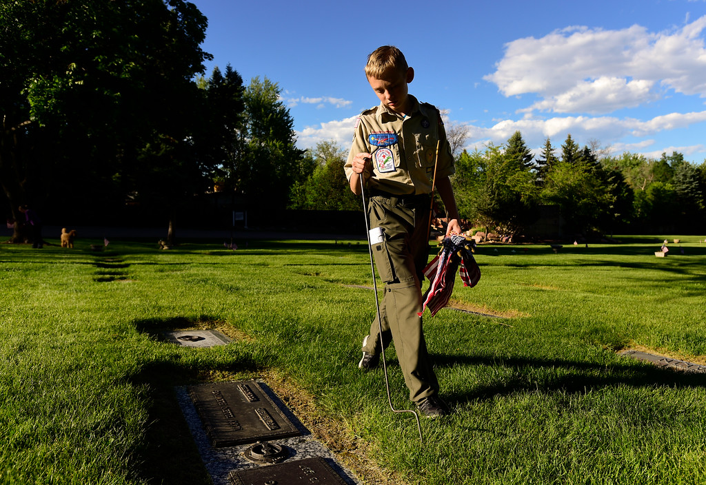 . Boy Scout Eliot Rowe, of Troop 77 Boulder Elks Lodge, searches for headstones of veterans at Green Mountain Cemetery in Boulder on Wednesday. Boy Scouts from Troop 77 placed flags on more than 480 graves of veterans of all branches of the armed services spanning from the Spanish American War to the present. More photos: DailyCamera.com. Matthew Jonas/Staff Photographer May 24,  2017