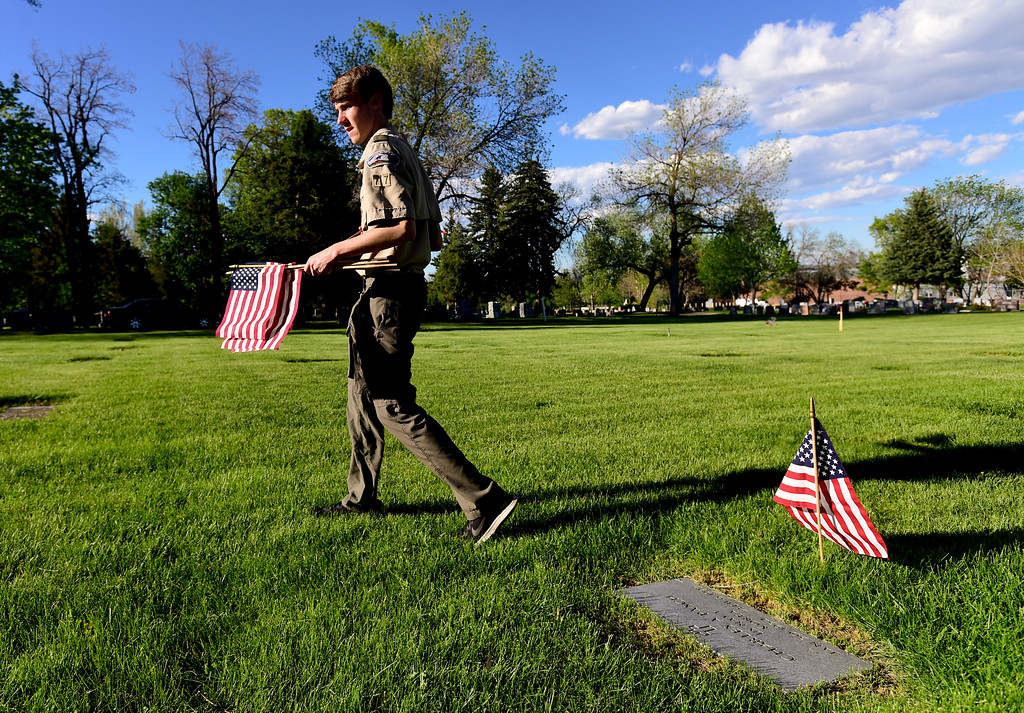 . Boy Scout Erik West, of Troop 77 Boulder Elks Lodge, searches for another headstone of a veteran after placing a flag at another at Green Mountain Cemetery in Boulder on Wednesday. Boy Scouts from Troop 77 placed flags on more than 480 graves of veterans from all branches of the armed services spanning from the Spanish American War to the present. More photos: DailyCamera.com. Matthew Jonas/Staff Photographer May 24,  20