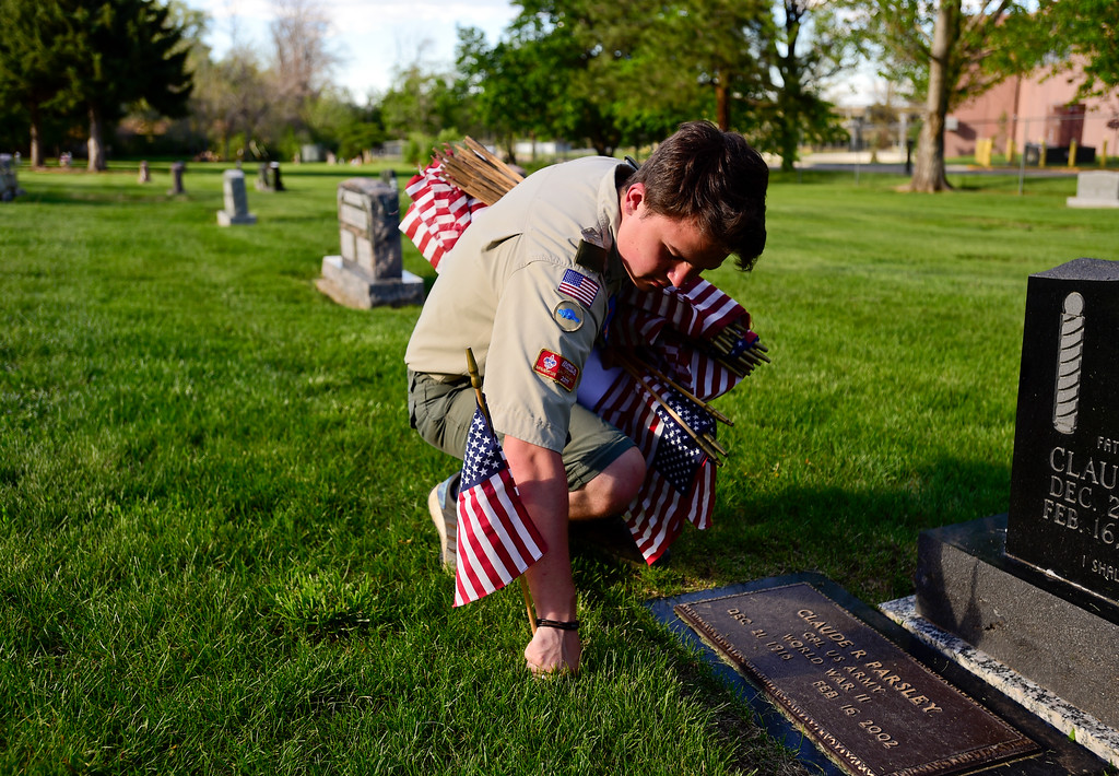 . Boy Scout Evan Stuber, of Troop 77 Boulder Elks Lodge, places flags at the headstones of veterans at Green Mountain Cemetery in Boulder on Wednesday. Boy Scouts from Troop 77 placed flags on more than 480 graves of veterans from all branches of the armed services spanning from the Spanish American War to the present. More photos: DailyCamera.com. Matthew Jonas/Staff Photographer May 24,  2017