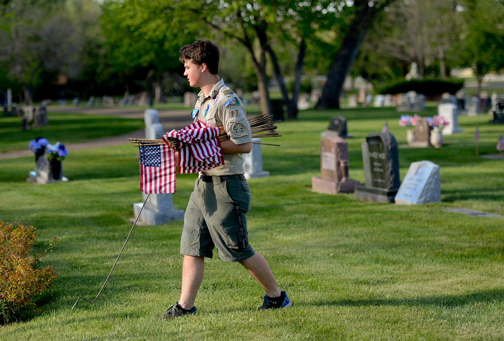 . Boy Scout Evan Stuber, of Troop 77 Boulder Elks Lodge, searches for  the headstones of veterans at Green Mountain Cemetery in Boulder on Wednesday. Boy Scouts from Troop 77 placed flags on more than 480 graves of veterans from all branches of the armed services spanning from the Spanish American War to the present. More photos: DailyCamera.com. Matthew Jonas/Staff Photographer May 24,  20