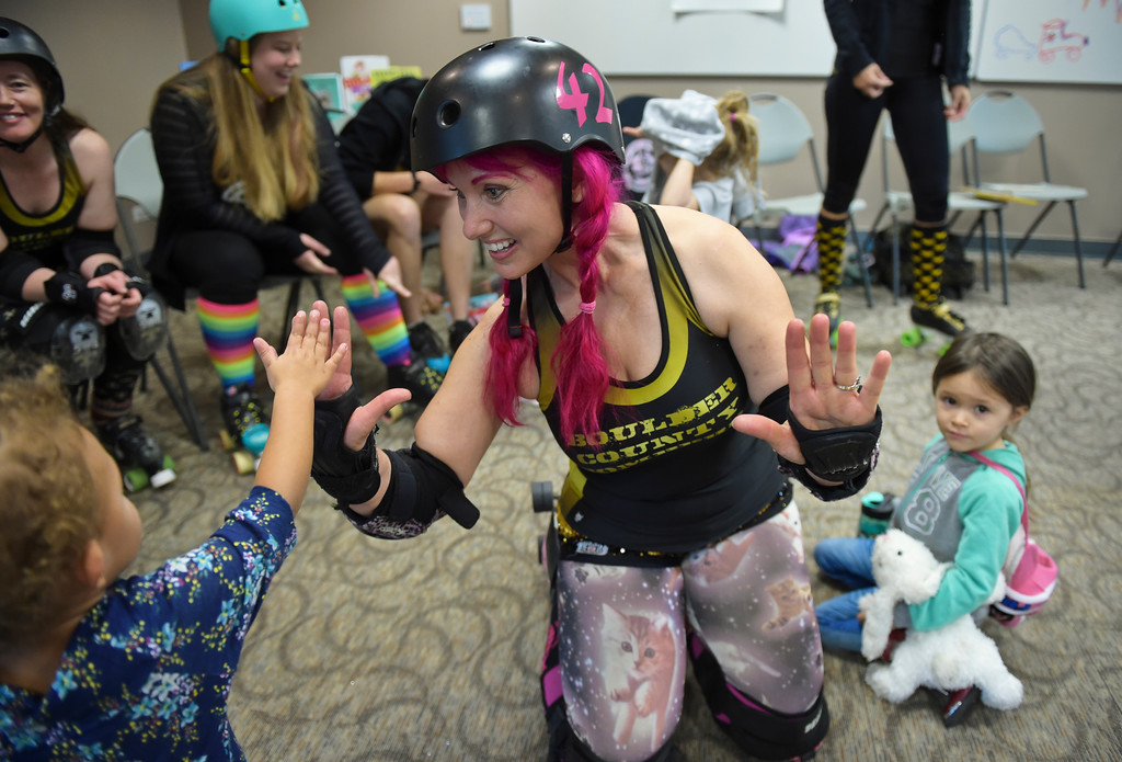 ". Zoe ""Pink Bang Theory\"" gets high fives after reading at the Longmont Public Library Wednesday morning. Several members of the Boulder County Bombers roller derby team read books pertaining to bullying, self confidence, feelings during the children\'s story time. \""We are now officially the coolest library in Boulder County if not Colorado,\"" said Electra Greer, head of children and teen services. To view more photos visit timescall.com.  Lewis Geyer/Staff Photographer Oct. 04, 2017"