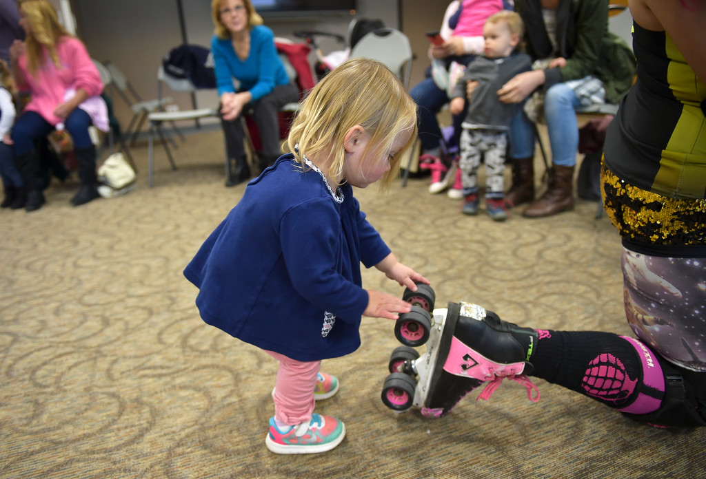 ". Grace Paige, 2, plays with the skates of Zoe ""Pink Bang Theory\"" Roberts at the Longmont Public Library Wednesday morning. Several members of the Boulder County Bombers roller derby team read books pertaining to bullying, self confidence, feelings during the children\'s story time. \""We are now officially the coolest library in Boulder County if not Colorado,\"" said Electra Greer, head of children and teen services. To view more photos visit timescall.com.  Lewis Geyer/Staff Photographer Oct. 04, 2017"