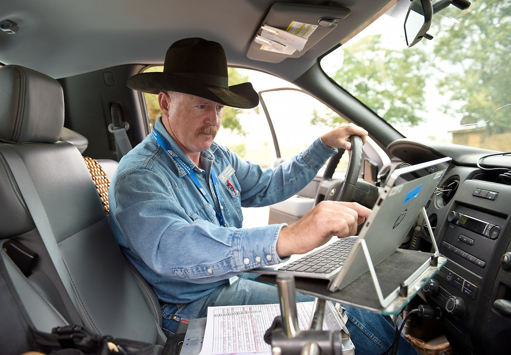 . LONGMONT, CO - AUG. 28, 2018: Brand inspector Chris Mace uses a laptop in his pickup to record the brands he inspected Aug. 28 at Ida Hoffman\'s ranch. The Brand Inspection Division employs 58 brand inspectors located throughout the state including 10 supervisors. (Photo by Lewis Geyer/Staff Photographer)