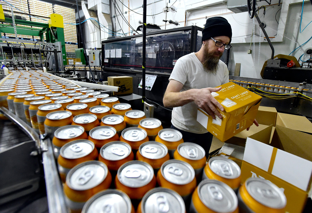. Todd Bills works to load a machine that boxes cans of beer at Upslope Brewing on Monday in Boulder. For more photos of activity at Upslope Brewing go to dailycamera.com Jeremy Papasso/ Staff Photographer/ Oct. 9, 2017