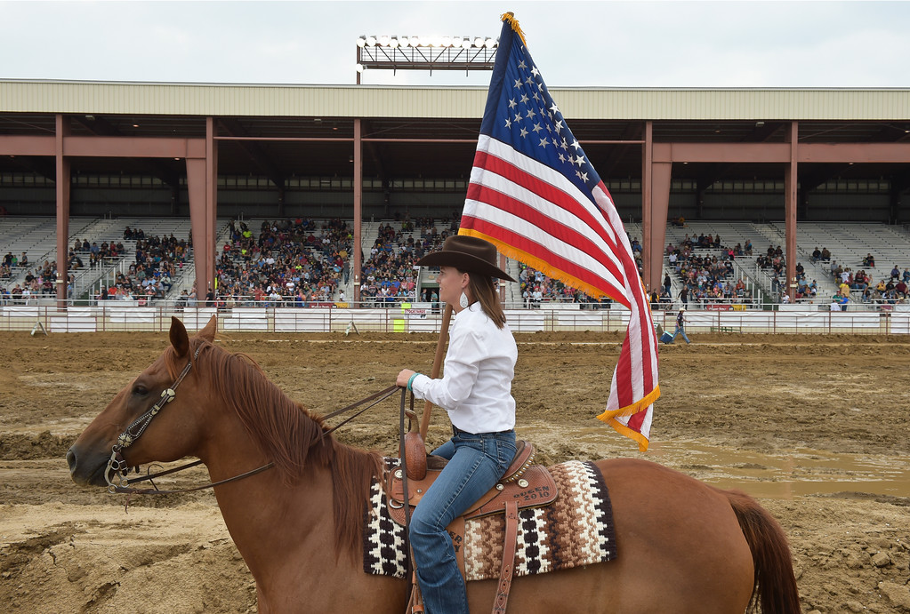 . Katie Richardson carries the American flag for the National Anthem at the start of the truck and tractor pull at the Boulder County Fair Sunday evening. Richardson was the 2010 Boulder County Fair queen. To view more photos visit timescall.com. Lewis Geyer/Staff Photographer August 06, 2017