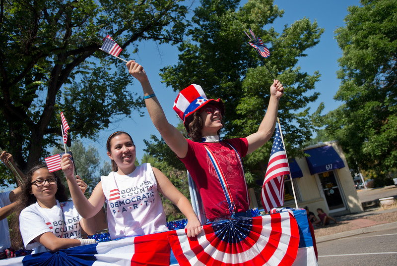 "People wave American flags as they greet the crowd on the Boulder County Democratic Party float during the Boulder County Fair Parade in Longmont on Saturday. <br /> More photos:  <a href=""http://www.dailycamera.com"">http://www.dailycamera.com</a><br /> (Autumn Parry/Staff Photographer)<br /> July 30, 2016"