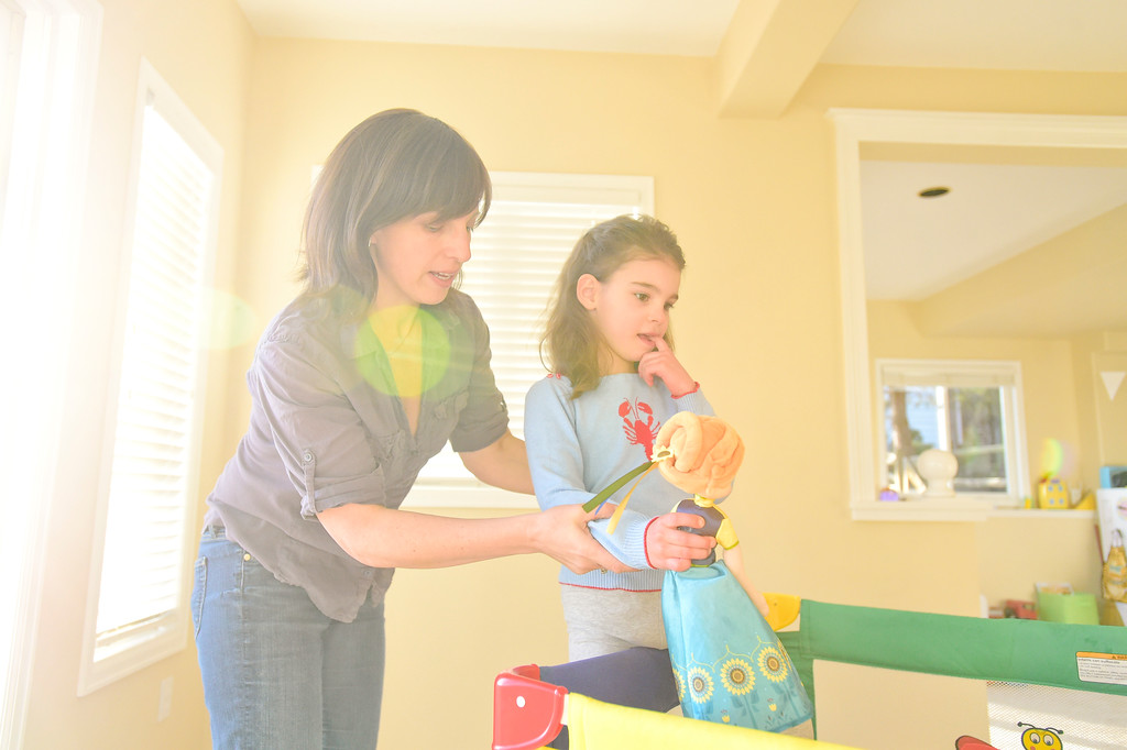 . Julia Vitarello, helps daughter Mila Makovec, 6, get into a crib filled with plastic balls at their home in Boulder County on Friday. Mila Makovec has been diagnosed with Batten disease, a terminal neurodegenerative disorder with no known cure. More photos: TimesCall.com. Matthew Jonas/Staff Photographer Jan. 13,  2017