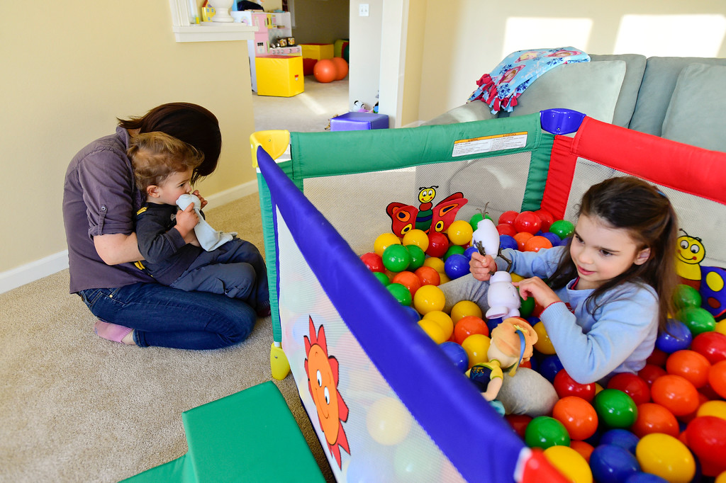 . Julia Vitarello holds Azlan Makovec, 2, as daughter Mila Makovec, 6, plays in a crib filled with plastic balls in their basement at their home in Boulder County on Friday. Mila Makovec has been diagnosed with Batten disease, a terminal neurodegenerative disorder with no known cure. More photos: TimesCall.com. Matthew Jonas/Staff Photographer Jan. 13,  2017