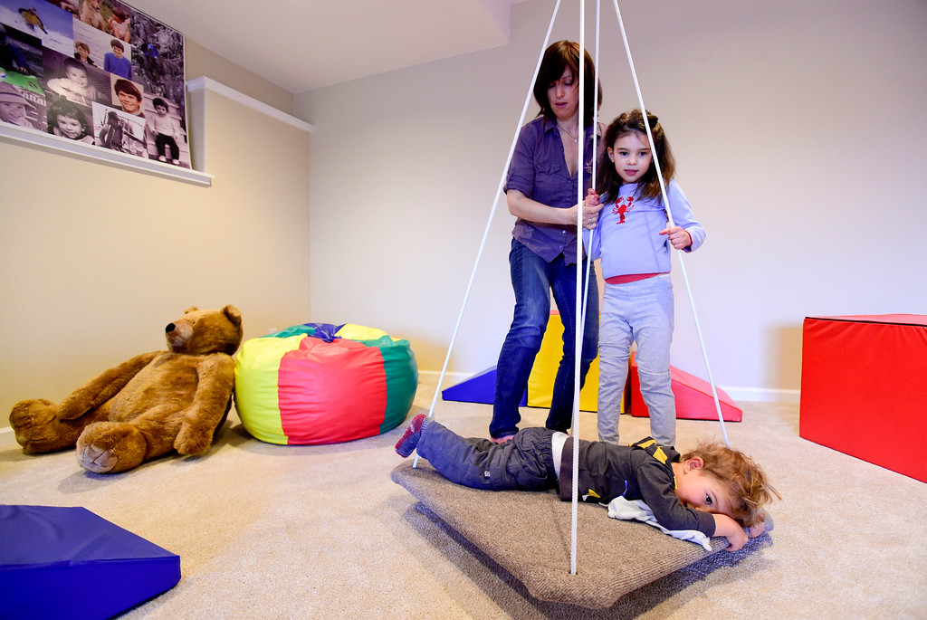 . Julia Vitarello plays with daughter Mila Makovec, 6, and Mila\'s brother, Azlan Makovec, 2, on a swing in their basement at their home in Boulder County on Friday. Mila Makovec has been diagnosed with Batten disease, a terminal neurodegenerative disorder with no known cure. More photos: TimesCall.com. Matthew Jonas/Staff Photographer Jan. 13,  2017