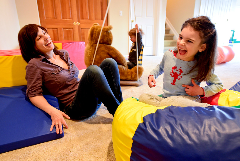 . Julia Vitarello, left, shares a laugh with daughter Mila Makovec, 6, right, as her brother Azlan Makovec, 2, plays on a swing at their home in Boulder County on Friday. Mila Makovec has been diagnosed with Batten disease, a terminal neurodegenerative disorder with no known cure. More photos: TimesCall.com. Matthew Jonas/Staff Photographer Jan. 13,  2017