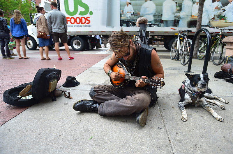 "Zachary Leatherwood, a homeless man, plays music while sitting next to his dog Julio on Pearl Street Mall in downtown Boulder on Friday. ""The happiest he's ever been is just out on the road, and I don't want to take that away from him,"" said Leatherwood, who is passing through the Boulder area.  <br /> More photos:  <a href=""http://www.dailycamera.com"">http://www.dailycamera.com</a><br /> (Autumn Parry/Staff Photographer)<br /> May 27, 2016"