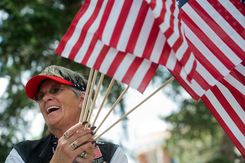 "Debra Allen, with the United States Veterans Riding Club, holds American flags which she gave away during the Boulder Creek Festival in Central Park on Sunday. The United States Veterans Riding Club honored Staff Sgt. Kenneth Mayne, of Arvada, with a cake on what would have been his 37th birthday. He died in 2008 while serving in Iraq. <br /> More photos:  <a href=""http://www.dailycamera.com"">http://www.dailycamera.com</a><br /> (Autumn Parry/Staff Photographer)<br /> May 29, 2016"