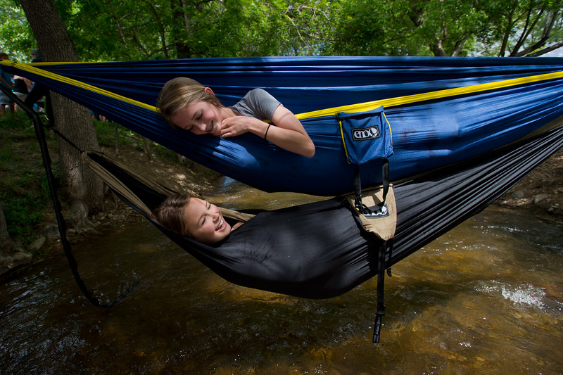 "Haven Lyon looks down at her friend, Tatum Glass, as they lay in hammocks that stretch across Boulder Creek in Central Park during the Creek Festival on Sunday.<br /> More photos:  <a href=""http://www.dailycamera.com"">http://www.dailycamera.com</a><br /> (Autumn Parry/Staff Photographer)<br /> May 29, 2016"