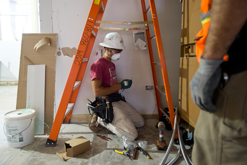 """Laurent Grosjean, a electrical apprentice, works on installing data drops in the library at Boulder High School on Thursday. <br /> More photos:  <a href=""""http://www.dailycamera.com"""">http://www.dailycamera.com</a><br /> (Autumn Parry/Staff Photographer)<br /> June 30, 2016"""