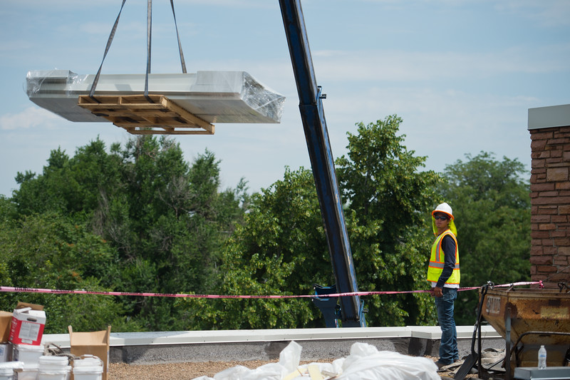 """Roof metal flashing is lifted to the roof to cap the perimeter during construction at Boulder High School on Thursday. Renovations at Boulder High are part of the first phase of school construction projects from 2014's $576 million bond issue. Boulder Valley has 22 projects under construction this summer.<br /> More photos:  <a href=""""http://www.dailycamera.com"""">http://www.dailycamera.com</a><br /> (Autumn Parry/Staff Photographer)<br /> June 30, 2016"""