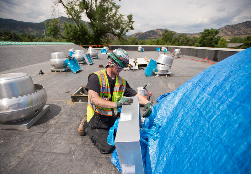 "Alan Wright installs curb extensions on the roof of Boulder High School on Thursday. Renovations at Boulder High are part of the first phase of school construction projects from 2014's $576 million bond issue. Boulder Valley has 22 projects under construction this summer.<br /> More photos:  <a href=""http://www.dailycamera.com"">http://www.dailycamera.com</a><br /> (Autumn Parry/Staff Photographer)<br /> June 30, 2016"