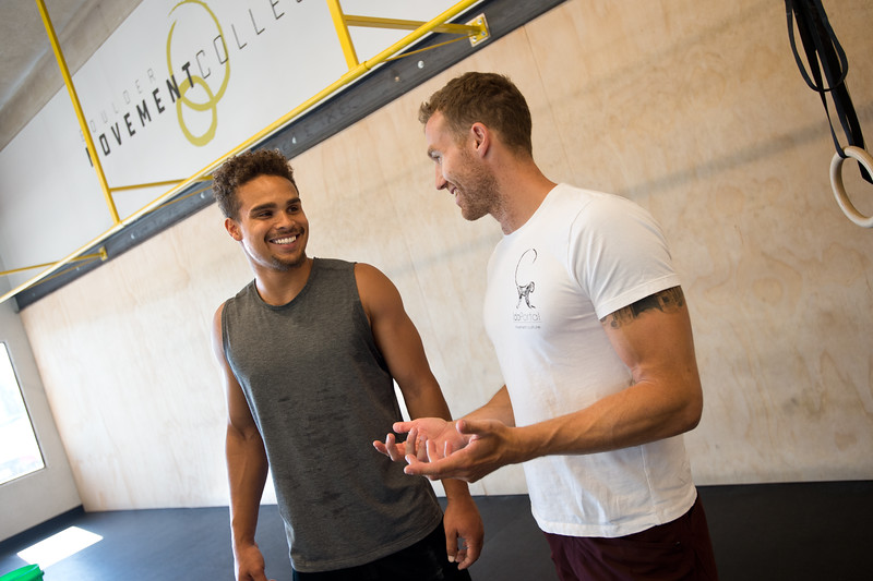 "Kain Colter talks with Matt Bernstein, co-owner and instructor, during a class at Boulder Movement Collective on Thursday. The classes are programed to have aspects of hand-balancing, mobility, gymnastic strength work and a movement focused skill aspect, with some coordination, locomotion patterns and dance foot work.<br /> More photos:  <a href=""http://www.dailycamera.com"">http://www.dailycamera.com</a><br /> (Autumn Parry/Staff Photographer)<br /> July 7, 2016"