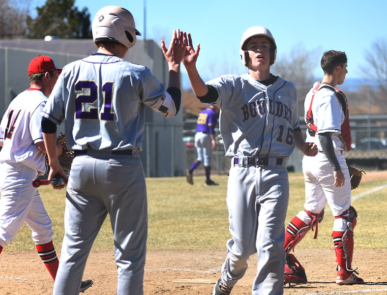Boulder's Dorsey Chatham congratulates teammate Sean Coan on scoring a run against Rangeview on Saturday, March, 17, in Aurora.