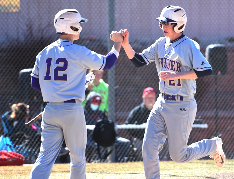 Boulder's Kyle Harris congratulates teammate Dorsey Chatham on scoring a run against Rangeview on Saturday, March 17, in Aurora.